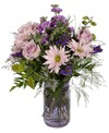 A 6-1/2in  purple vintage jardin vase holds an all around arrangement with two roses, stock, daisy poms, eryngium, hypericum, statice, caspia, bupleurum, and tree fern. 16in H x 10in W